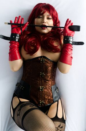Red-haired woman in a red wig, corset and leather gloves posing lying on a bed holding a stick in the hands of a whip. Bdsm outfit Stock Photo