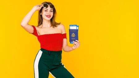 Portrait of a happy young woman holding traveling tickets and passport isolated over yellow background. Focus on passport.