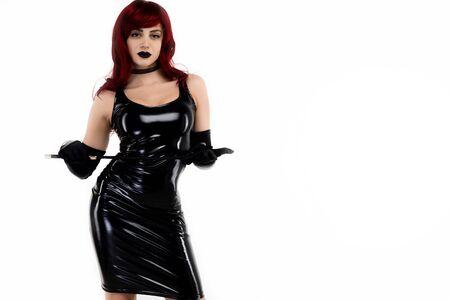 Signora appassionata dai capelli rossi in un vestito di lattice nero in posa con una frusta in mano su uno sfondo bianco