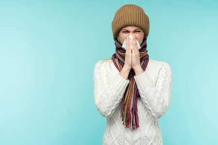 Health and medicine concept - Young woman blowing nose into tissue, on a blue background. Pretty girl cold with snot.