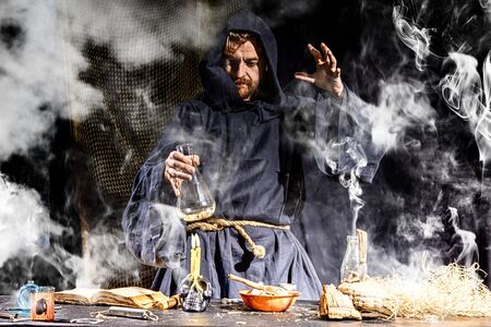 The medieval alchemist make magic ritual at the table in his smoke laboratory. Halloween concepy background.