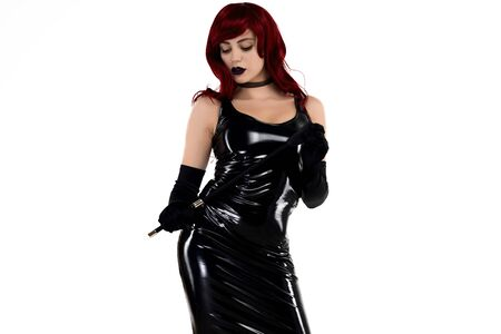 Red-haired passionate lady in a black latex dress posing with a whip in her hands on a white background