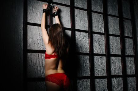 BDSM outfit for adult sex games. A young woman chained to the bars with handcuffs with bondage awaiting punishment. - Image Stock Photo - 129712513
