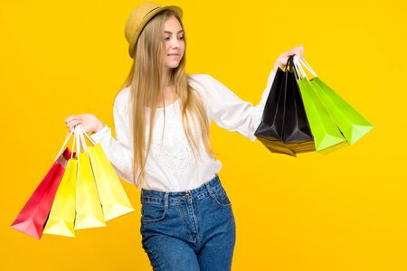 Caucasian teenage girl on yellow background. Stylish young woman with shopping bags in hands - image
