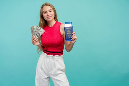 Exchange Learning Concept. Studio portrait of pretty young student woman holding passport with tickets and money. Isolated on bright blue background. Stock fotó