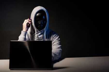 Anonymous hacker in mask programmer uses a laptop and talking on the phone to hack the system in the dark. The concept of cybercrime and hacking database