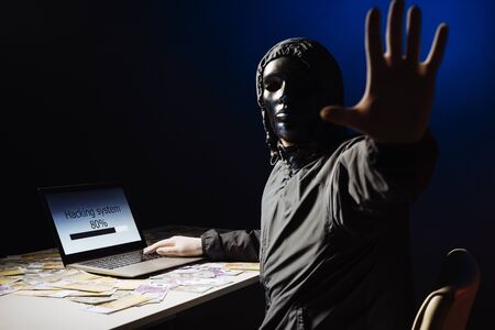 Anonymous hacker programmer uses a laptop to hack the system in the dark. The concept of cybercrime and hacking database. Money is scattered on the table. Focus on laptop