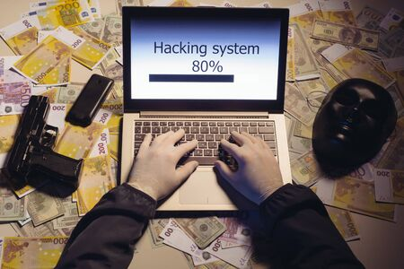 Top view on the hands of an attacker programmer hacking a data server from his laptop. Money is thrown on the table, lies a telephone, a gun, and a mask. The concept of cybercrime and hacking database