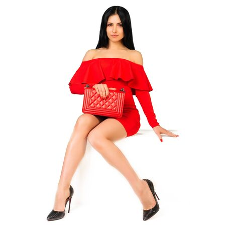 Beautiful woman wearing red dress with purse hand bag with high heels shoes sitting on the white bench - image Stock Photo