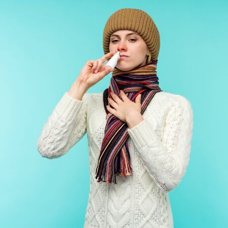 Sick young woman in scarf and hat use nasal spray isolated on blue background - image