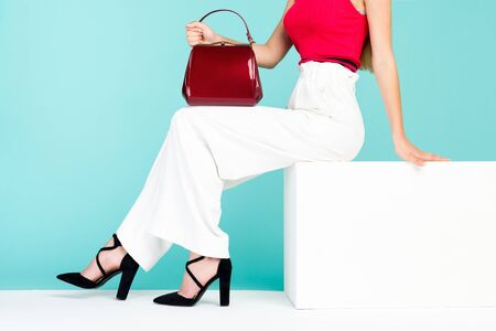 Beautiful legs woman sitting on the bench. With red purse and high heel shoes. - image