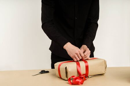 Young Asian man packs a gift parcel on the table - Image