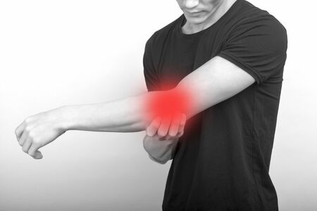 male having elbow pain in injured arm on background - image