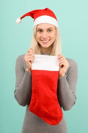 A beautiful sexy girl in a New Years hat and gray dress hold in hands a Christmas sock. Celebration of Christmas or new year - image