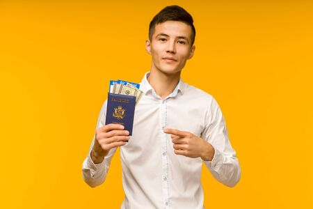 A handsome asian man in a white shirt rejoices in winning the lottery. He is pointing on a passport with air tickets and money dollars on a yellow background. - image