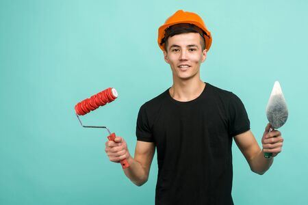 Asian working man in an orange helmet stands with a paint roller and trowel on a blue background - image Banco de Imagens