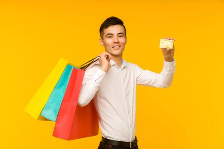 Young asian man showing his shopping bag and credit card on yellow background