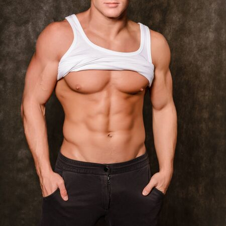 Handsome young man taking off white t-shirt