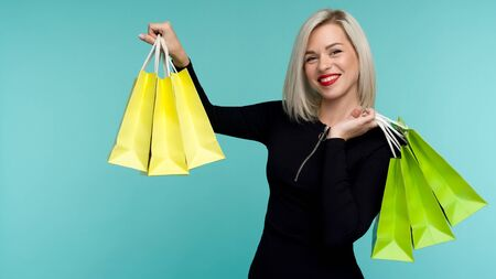 Sale. Young smiling woman holding shopping bags in black friday holiday. Happy Girl on blue background
