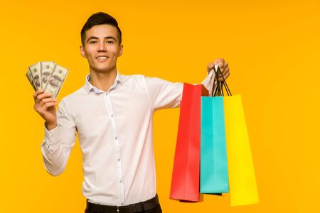 Young asian man showing his shopping bag and money on yellow background Stock fotó