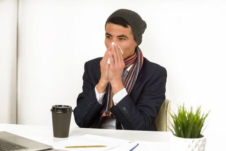 Young asian business man blows his nose while working on laptop at the office. - image Foto de archivo - 131332112