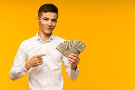 Joyful asian man in a white shirt points a finger at money dollars on a yellow background - image 写真素材