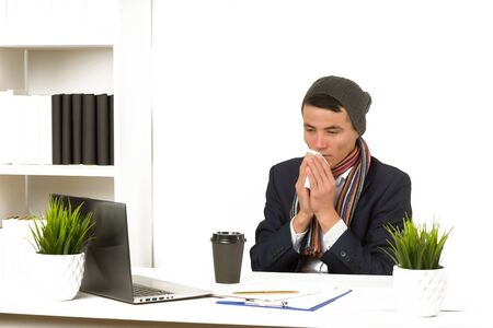 Young asian business man blows his nose while working on laptop at the office. - image