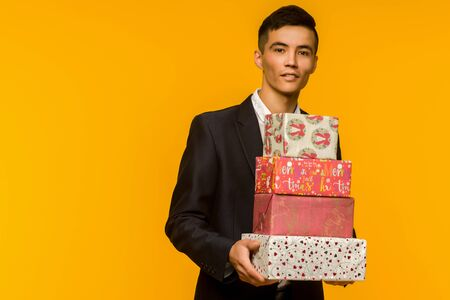 Handsome asian businessman holding gift box over yellow background - image Banque d'images - 131952568