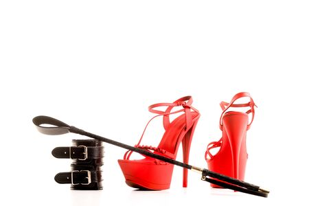 BDSM outfit for adult games. Red high-heeled striptease shoes and handcuffs, whip isolated on a white background - image
