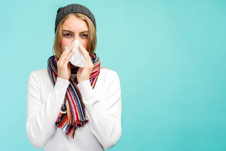 Health and medicine concept - Sad Teen Girl blowing nose into tissue, on a blue background. Pretty girl cold with snot. - image