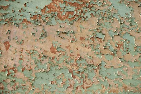 Textured wall with colorful paint, parts falling off flakes away from old age. - image