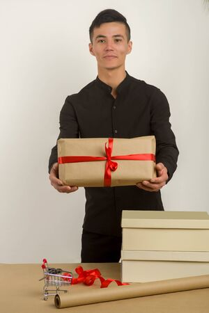 Young Asian man holds a gift parcel in hands - Image