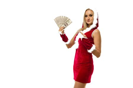 A beautiful sexy girl in a New Year's dress points a finger at money isolated on white. Celebration of Christmas or new year