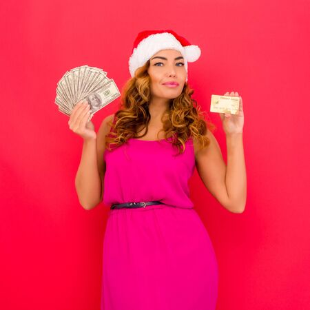 A beautiful sexy woman in a New Year's hat, hold in hands money and credit card isolated on red. Celebration of Christmas or new year Stock Photo