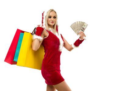 Una mujer hermosa en un vestido de año nuevo, mantenga en las manos dinero y bolsas de compras aisladas en blanco. Celebración de la venta de Navidad o año nuevo