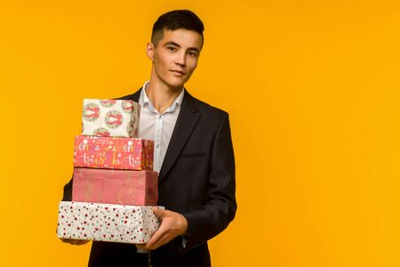 Handsome asian businessman holding gift box over yellow background - image