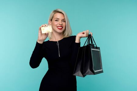 Image of a beautiful happy young blonde woman posing isolated over blue wall background holding shopping bags. Black Friday Holiday Concept. Sale Zdjęcie Seryjne