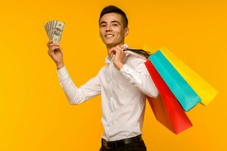 Young asian man showing his shopping bag and money on yellow background Stok Fotoğraf