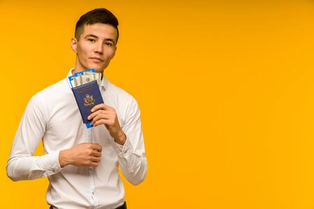 A handsome asian man in a white shirt rejoices in winning the lottery. He is holds a passport with air tickets and money dollars on a yellow background. - image Stok Fotoğraf