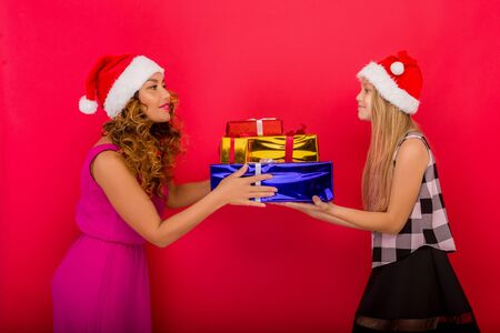 Merry Christmas and Happy Holidays. Cheerful mom and her cute daughter girl holding Christmas gift. Red background Фото со стока
