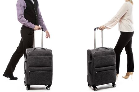 Handsome man and woman walking with luggage. Side view of young couple on white background - image