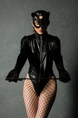 Adult sex games. Beautiful dominant brunette vamp mistress girl in latex body, gloves and bdsm black leather fetish cat mask posing with riding crop. - image