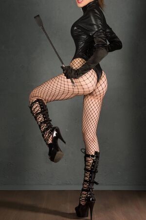 Beautiful sexy dominant vamp mistress dominatrix bdsm woman model with spank and high heels posing back , sex shop concept. - image