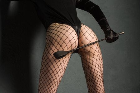 Adult sex games. Sexy girl ass in fishnet and leather body with whip prepare for punishment. - image