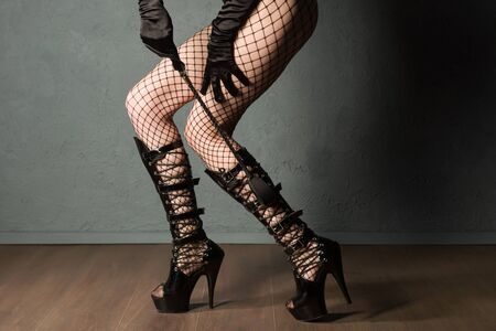 Adult sex games. Sexy girl legs in fishnet and high heels fetish boots with whip prepare for punishment. - image Zdjęcie Seryjne