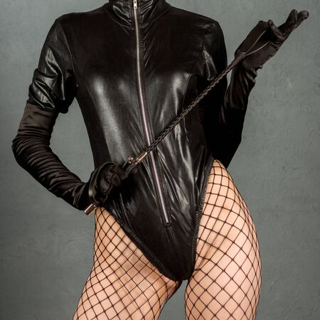 Adult sex games. Beautiful dominant brunette vamp mistress girl in latex body, gloves posing with riding crop. - image