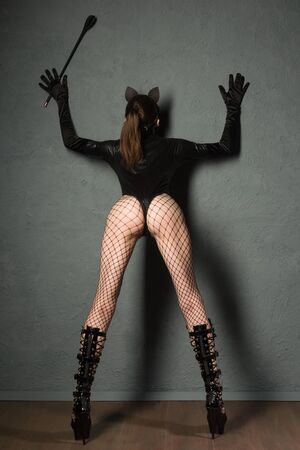 Adult sex games. Sexy girl standing back in fishnet and high heels boots with whip prepare for punishment. - image