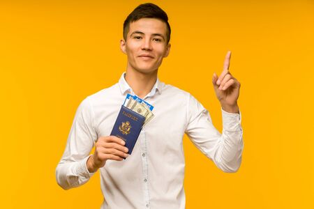 A handsome asian man in a white shirt rejoices in winning the lottery. He is pointing up holds a passport with air tickets and money dollars on a yellow background. 免版税图像