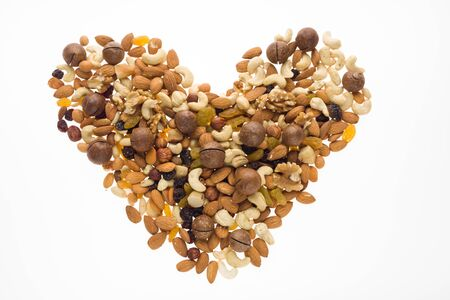 Mix of nuts and dried fruits in the shape of a heart. Cashew, almonds, macadamia, hazelnuts, Brazilian, walnuts, raisins, peanuts Foto de archivo - 135502396