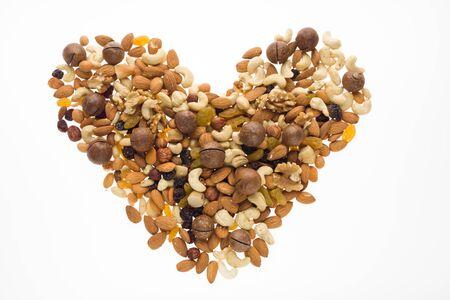 Mix of nuts and dried fruits in the shape of a heart. Cashew, almonds, macadamia, hazelnuts, Brazilian, walnuts, raisins, peanuts Reklamní fotografie